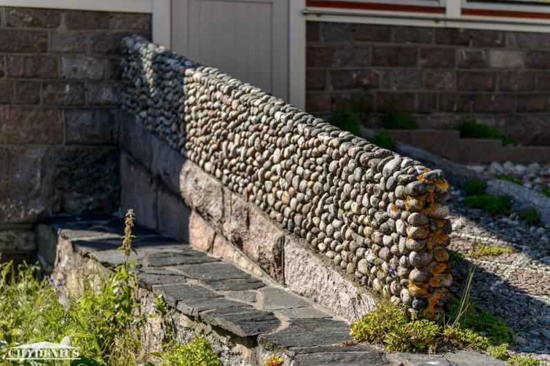 Taitavan muurarin kädenjälki näkyy kaikkialla. Tässä pyörökiveä ja kivimosaiikkia puutarhan ovella